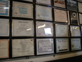 A wall is covered with one fleet technician's awards and certificates.