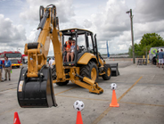 Caterpillar challenged attendees with a game: can you get the soccer balls in the bucket?