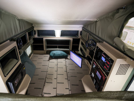 The inside of the vehicle includes a bed and first aid kit for on-site care and a refrigerator...