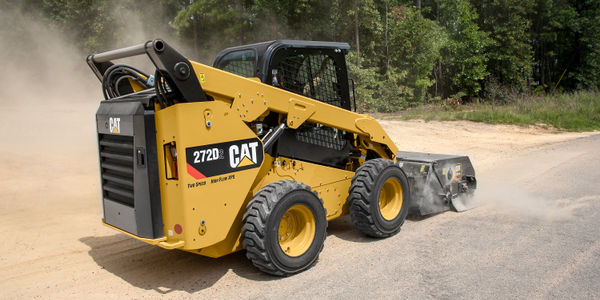 Cat 272D3 SSL with a utility broom in a working application. Photo courtesy of Caterpillar