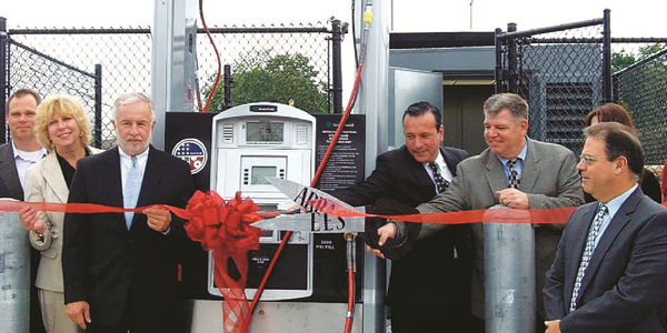 Community leaders gather for the grand opening of a compressed natural gas fueling station at...