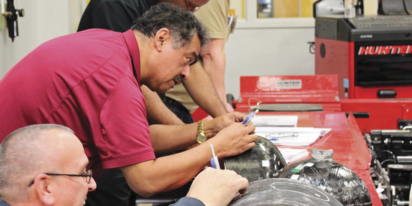 During hands-on practical skill building, technicians use a depth gauge to assess damage on a...