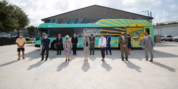 Officials stand in front of the new SunRunner BRT bus.