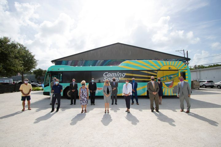 Officials stand in front of the new SunRunner BRT bus. - PSTA