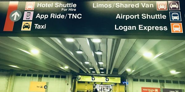Boston's Logan Airport signage directs passengers to various transportation modes, including TNCs.
