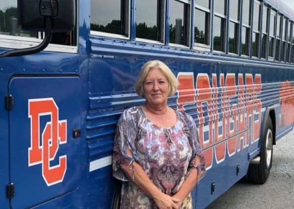 Dickson County Schools Transportation Coordinator Melissa Garton is shown here with one of two new activity buses being used to transport high school students on sports trips since the first day of school on Aug. 3. - Photo courtesy Melissa Garton
