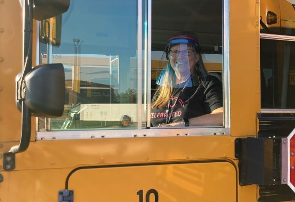 Piqua Transportation Director Beth Cain displays a face shield that some of the district's drivers will wear this school year. Others will don masks emblazoned with the district's mascot. - Photo courtesy Beth Cain