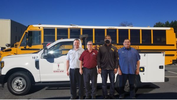 Gwinnett County (Ga.) Public Schools mechanic Calvin Cornelius (third from left) was assisted by his coworkers when he had a heart attack on the job. (Shown left to right: Mitchell Edwards, Buddy Marino, and Martin Piedra.) - Photo courtesy Gwinnett County Public Schools