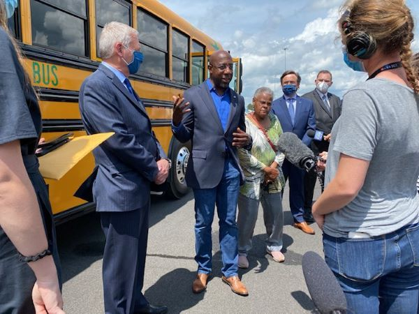 Sen. Raphael Warnock (shown center) visited Blue Bird Corp.'s manufacturing facility in Fort Valley, Georgia, and got a firsthand look at electric school bus technology. Picturedleft is Phil Horlock, Blue Bird's president and CEO. - Photo courtesy Blue Bird