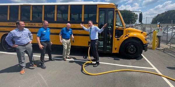Sen. Mark Warner (right) is shown here plugging in one of Virginia's Jouley electric school...