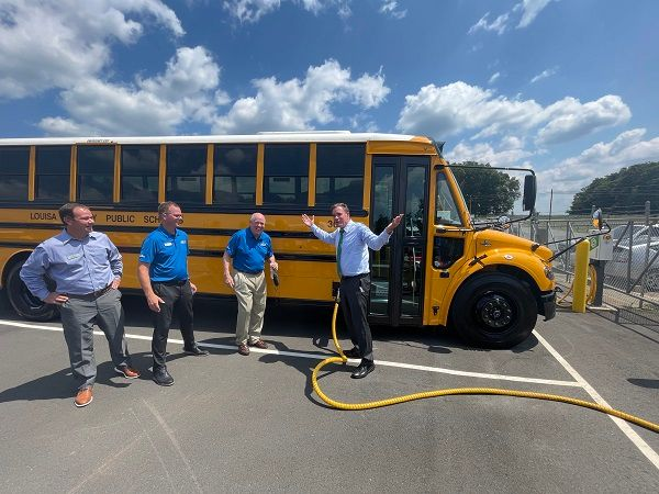 Sen. Mark Warner (right) is shown here plugging in one of Virginia's Jouley electric school buseswith Floyd Merryman, executive chairman of Sonny Merryman Inc.; Caley Edgerly, the company's president and CEO; and Eric Reynolds, senior director of Proterra. - Photo courtesy Sonny Merryman Inc.