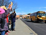 Waving signs and clapping their hands, students from Ryder Elementary School showed their...