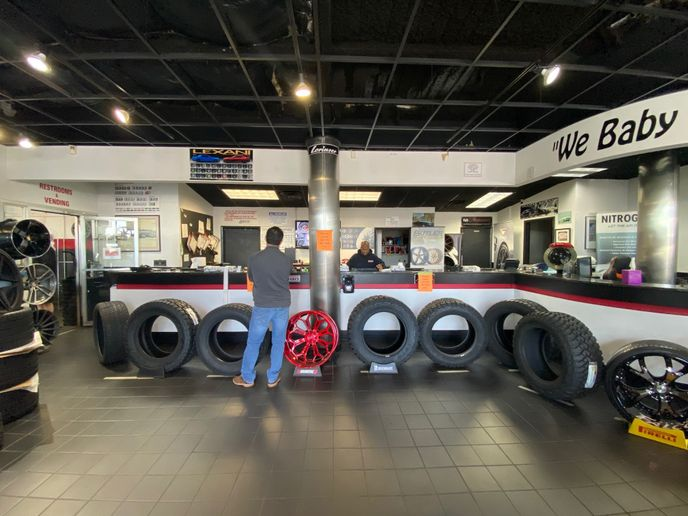 "Butler Tire built a ""wall"" of light truck tires to enforce social distancing at its sales counters. -"