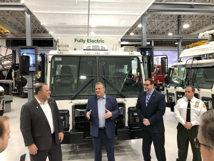 Rocky DiRico, deputy commissioner of the New York City Department of Sanitation (center) explains to journalists how the LR Electric will have to do double duty as a refuse collector and a snow plow. - Photo: Jim Park