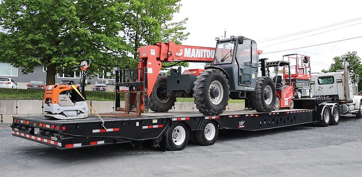 The main feature of this custom Manac trailer is the 14-foot-long rear bi-fold hydraulic ramp constructed of steel traction plate that boasts a capacity of 20,000 pounds with a low load angle. The trailer also features 8-foot hydraulic ramps located in the front of the lower deck that can be activated so machinery can be loaded over the front neck of the trailer, allowing for full use of the available deck space. - Photo: Manac