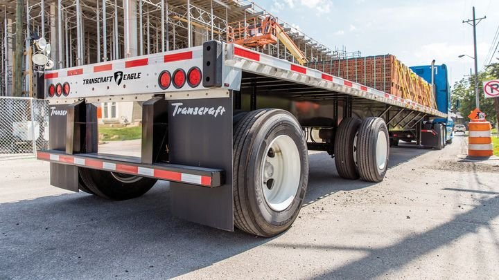 Wabash National's re-engineered Transcraft Eagle flatbed trailer will have new features for the 2021 model, which includes a lighter weight design, more load securement versatility, a high standard beam rating, additional side turn/marker lamps for better visibility, and limited-lifetime beam and five-year wheel-end warranties. - Photo: Wabash International