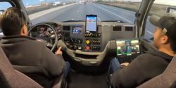 A TuSimple test driver (on the left) and software tech (right seat) pair to both keep the truck...