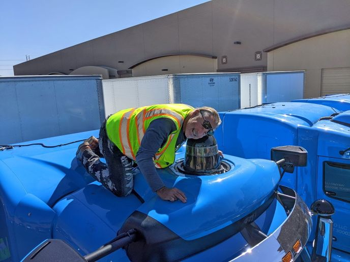 Waymo Via safety driver trainer, Jon Rainwater, inspects one of the sensors on the truck prior to a trip. 
