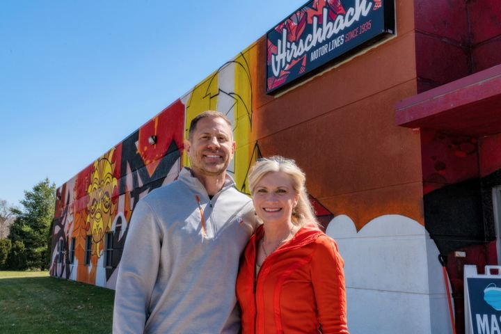 Brad Pinchuk and wife Jillayne next to an original mural on the wall of a building at Hirschbach's East Dubuque, Illinois, campus. - Photo: Hirschbach