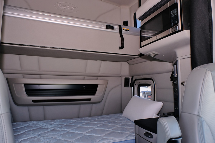 The living quarters are roomy and quiet. The upper bunk can serve as additional storage space when not occupied by a co-driver.