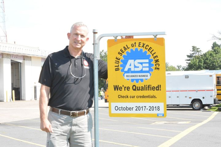 Paul Cupka stands proudly in front of the ASE Blue Seal of Excellence at the Fairfax County facility, which is also currently under construction.