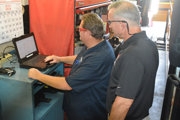 John Wingard (left) and Paul Cupka at the dynamics station, where they put school buses in gear on a treadmill to test engine functions.