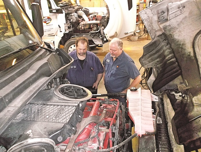 From left, Jeff Rickey, a Tier 5 senior truck technician, and David Northcut, shop manager, diagnose an engine control module on one of the company's trucks at the Schilli NationaLease shop in Remington, Indiana. Photo: Schilli