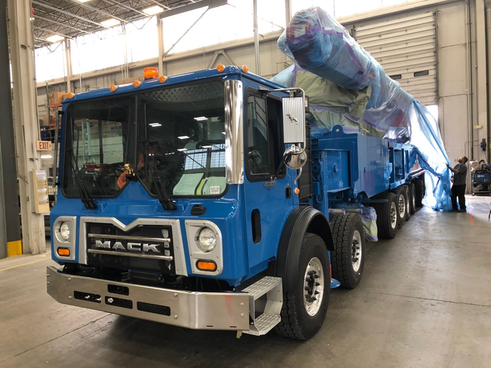 A member of the Putzmeister production team removes the wraps from a freshly painted concrete pump destined for Pompages De Beton in Quebec.  - Photos via Today's Trucking