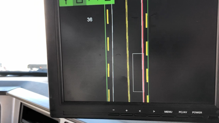 In the cab, drivers have a display that shows the truck's position relative to the lane markings on a moving map. The center-line appears as a double yellow dashed line, while the outer lane markings appear as solid white lines. The white rectangular box is a scale representation of the truck. The solid green line represents the guardrails. If the truck crosses over the lane marking, a solid red line appears warning the driver he or she is crossing out of the prescribed lane.