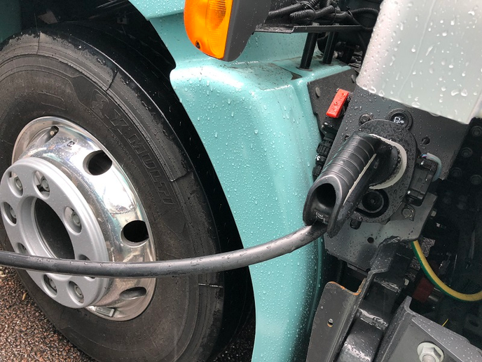 It takes between 10 and 12 hours to fully recharge a Volvo electric truck, via a three-prong charger that plugs into a socket located immediately behind the driver-side door.