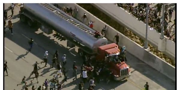 Even before the truck came to a stop, protesters started swarming it and pulled the driver from...