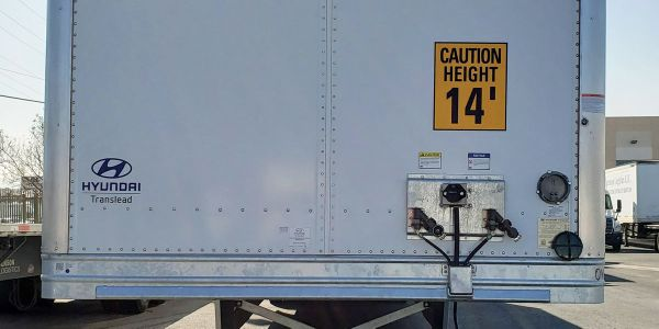 The front of the trailer bears a warning about the height.