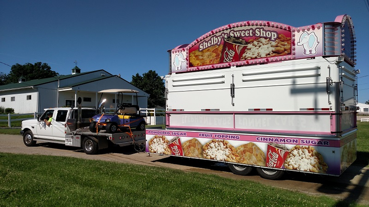 "Ford F-350 with an aluminum flatbed trailer toting a golf cart and hitched to a ""funnel cake"" trailer.