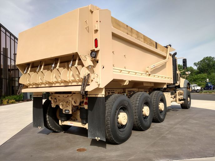 Crysteel bodies on the U.S. Army's latest heavy dump trucks are made of AR 450 abrasion-resistant, high-strength steel. Tail gates allow volume dumping or any of four driver-controlled chutes can be opened for laying down one or more furrows of aggregates on roads and trails. Pintle hitch and air glad hands allow for towing of equipment trailers.