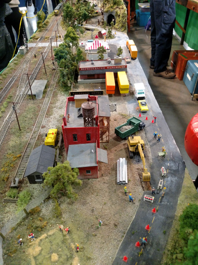 "A fairly realistic construction scene includes a dump truck, workers in hard hats, orange traffic cones, and an excavator digging a trench. But, check the dry van trailers backed against the loading dock of the ""refrigerated warehouse."" Spoiled goods, anyone?   - Photo by Tom Berg"