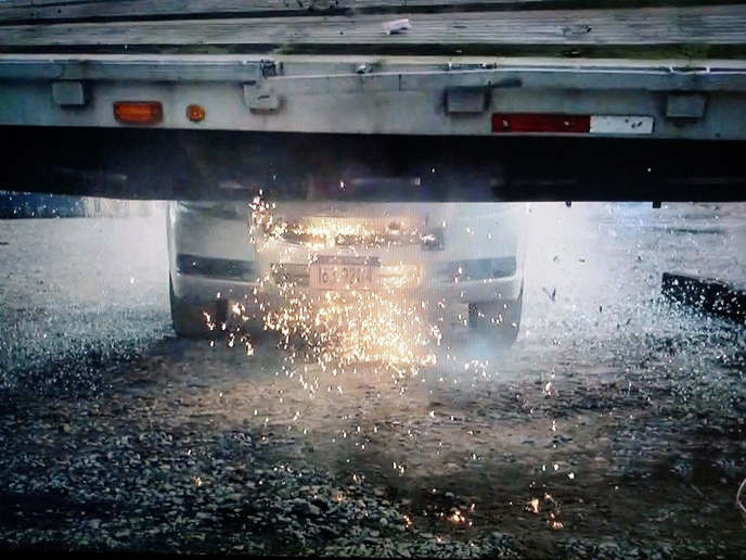 Debris flies as the fictional suspect's car hits the other side of the steel flatbed. The scene was shot using four or five cameras, including those inside the cars. Oh -- did the impact pop the weld under that bent rub rail? More likely it was busted in years of hard, real-world service in New York City.  -