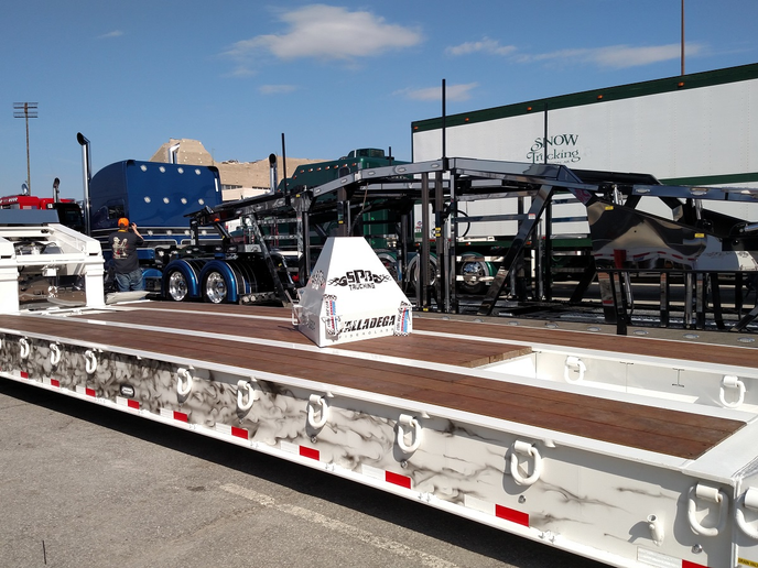This lowboy sports pearlesque paint that matches the décor on the tractor. Would you want to load a dirty excavator onto this beautiful trailer? And note the bright-metal accents on the auto carrier next door.  -