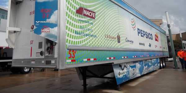 Advanced-technology trailer on display at a trucking show has nose fairings, side skirts, and...