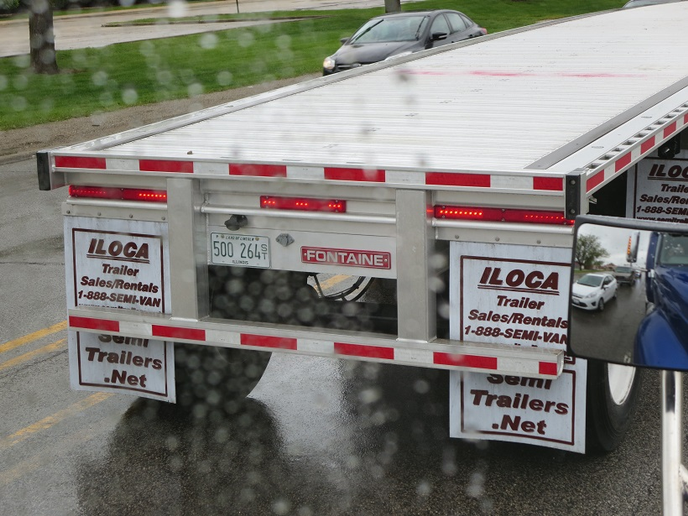 """Wheels back"" trailer like this spread-axle flatbed doesn't legally need a rear impact guard or a label because its tires and rear-most axle would stop a car from plowing under the trailer.  In underride accidents, motorists are usually killed or badly injured.