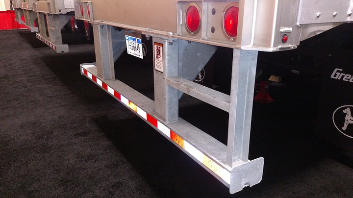 "Rear impact guard on this van trailer complies with a 1998 federal safety standard that requires certain energy absorption performance. A special label on the front of the bumper says so by including the letters, ""DOT.""