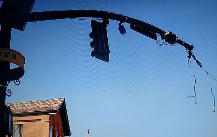 Wires dangle from a horizontal light pole, which also has a void where the traffic signal light was.