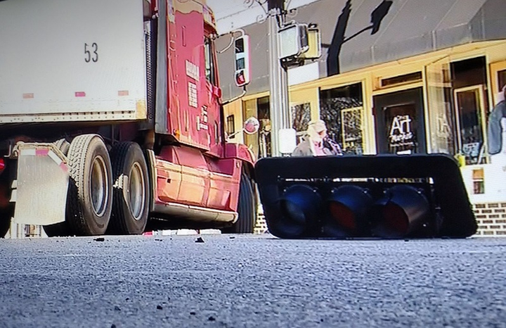 A semi has stopped in an intersection in Westerville, Ohio, after it snagged a low-hanging wire and pulled down a traffic signal light. It's the black object laying on the pavement to the right.