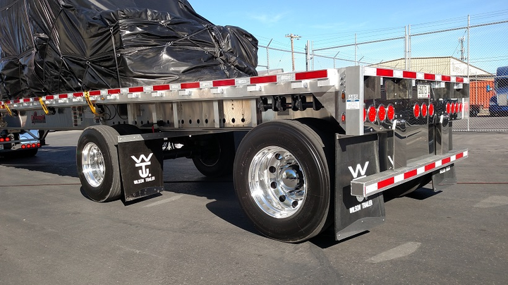Common spread-axle flatbeds, like this Wilson aluminum unit, have a rear-set axle and wheels whose tire surfaces are within 12 inches of the trailer's rear.Thus it's exempt from needing an impact-absorbing guard. This bumper appears stout, but it needn't be energy absorbing as described by motor vehicle safety standards.  -
