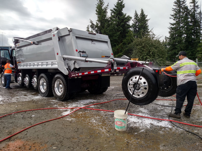 "New additions are a pair of ""super solo"" straight trucks, like this one getting a bath. They have seven axles, including the swing-down ""booster,"" and can gross 82,000 pounds while carrying a 26-ton payload, says the fleet's operations manager. Most power units are Mack Granites.