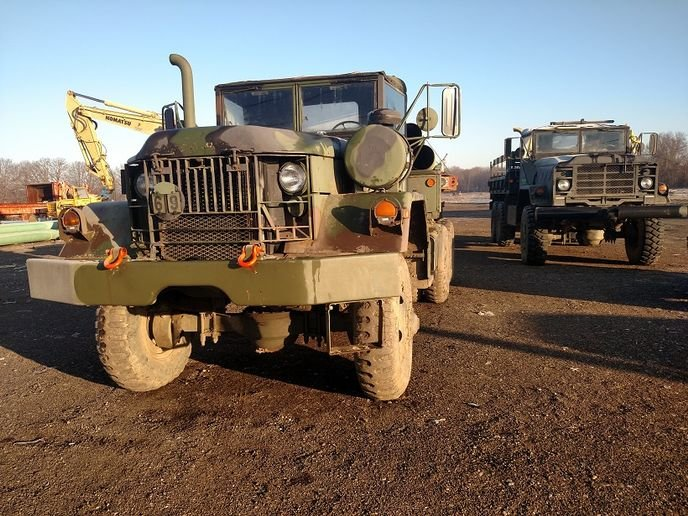 This pole trailer is hitched to an ex-military tractor, a 5-ton 6x6 well suited for off-road service. Next to it is a 5-ton 6x6 cargo truck. Both are owned by a pipeline contractor.  -