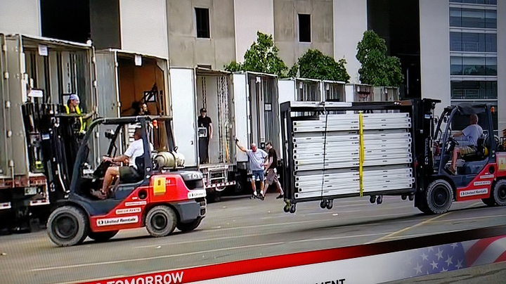 Roadies and local workers unload gear for setup inside the stadium. About 60,000 fans attended the show, local media reported.