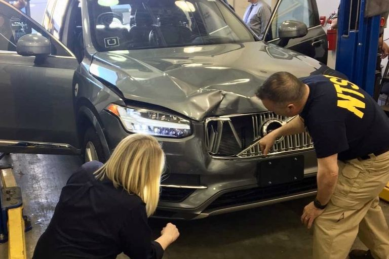 NTSB Investigators examine the Volvo XC90 sedan involved in a fatal crash on March 18, 2018,...