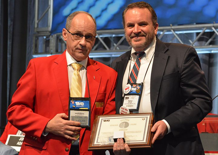 Peter Savage, director of quality and implementations at Clarke Power Services, accepts his award from TMC Chairman Ken Calhoun. - Photo: ATA