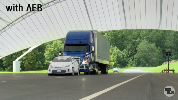 """In an Insurance Institute for Highway Safety test of automatic emergency braking, a truck with AEB came to an emergency stop behind the test """"car,"""" lights flashing and horn sounding, without the truck driver touching the brake pedal. - Screen shot from video of IIHS AEB testing"""