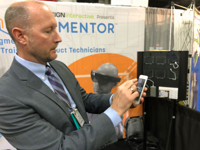 Matt Johnson, division head of commercial solutions, demonstrates the company's augmented reality smartphone technology for technician training.
